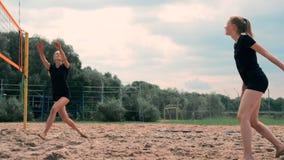 Mulheres que competem em um competiam profissional do voleibol de praia Um defensor tenta parar um tiro durante as 2 mulheres vídeos de arquivo