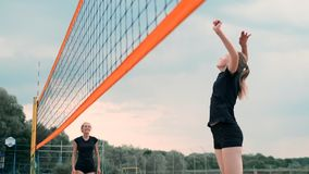 Mulheres que competem em um competiam profissional do voleibol de praia Um defensor tenta parar um tiro durante as 2 mulheres filme
