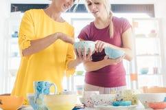 Mulheres que compram pratos cerâmicos em uma oficina imagens de stock royalty free