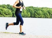 Mulheres que correm em uma fuga ao lado da água fotos de stock royalty free