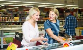 Mulheres que escolhem a carne congelada Imagem de Stock