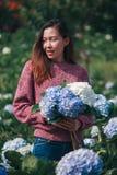Mulheres que estão guardando flores da hortênsia no jardim fotos de stock