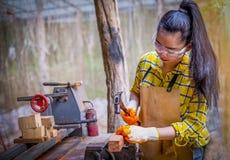 Mulheres que estão o construtor que veste o trabalhador verificado da camisa do canteiro de obras que martela o prego no de madei imagens de stock