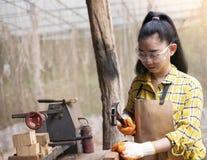 Mulheres que estão o construtor que veste o trabalhador verificado da camisa do canteiro de obras que martela o prego no de madei imagens de stock royalty free