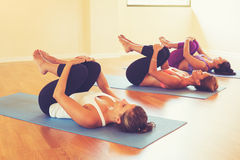 Mulheres que esticam e que relaxam na classe da ioga