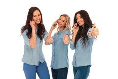 3 mulheres que falam no telefone que faz o sinal aprovado Fotos de Stock Royalty Free