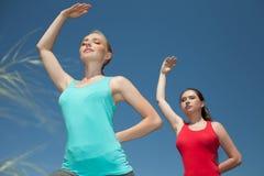 Mulheres que fazem a estada da foto da ioga fora e as poses das mostras fotografia de stock
