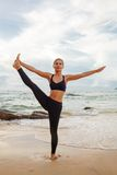 Mulheres que fazem a ioga com o oceano atrás Fotografia de Stock Royalty Free