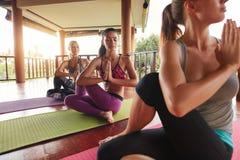 Mulheres que fazem a ioga na pose da torção na esteira Fotos de Stock