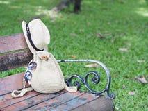 Mulheres que fazem malha o saco e o chapéu no banco de madeira do vintage no parque imagem de stock royalty free