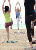 Mulheres que fazem o exercício da aptidão em uma praia Imagens de Stock