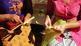 Mulheres que fazem ofertas do sari de Canang do balinese, fim acima filme