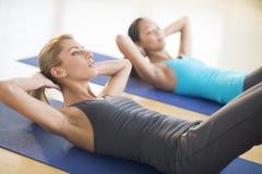 Mulheres que fazem Sentar-UPS no health club imagem de stock royalty free