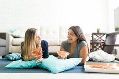 Mulheres que guardam fatias da pizza ao encontrar-se no assoalho durante o partido fotos de stock royalty free