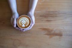 mulheres que guardam o copo de café, café de madeira da tabela ao ter o coffe imagem de stock royalty free