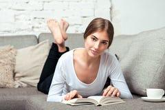 Mulheres que lêem um livro no sofá fotos de stock