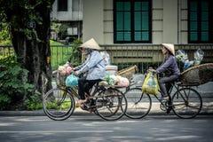 Mulheres que montam bicicletas na rua em Hanoi fotografia de stock