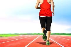 Mulheres que movimentam-se em pistas de atletismo Imagem de Stock