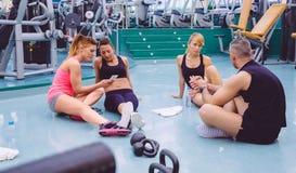 Mulheres que olham amigos do smartphone e dos pares Fotografia de Stock Royalty Free