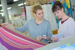 Mulheres que olham matérias têxteis fotos de stock royalty free