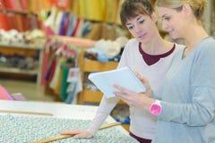 Mulheres que olham notas e que medem o material fotos de stock royalty free