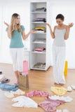 Mulheres que olham para baixo no saco de compras e na roupa no assoalho Imagem de Stock Royalty Free