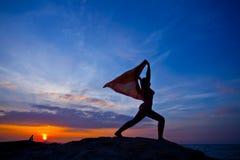 Mulheres que praticam a ioga no por do sol Imagens de Stock Royalty Free