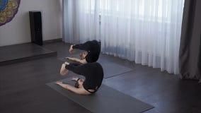 Mulheres que praticam o lance da ioga seus pés atrás de suas cabeças, para fazer algum asana video estoque