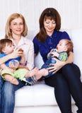 Mulheres que prendem bebês Imagem de Stock Royalty Free