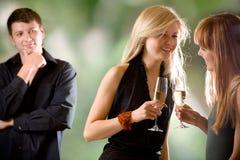 Mulheres que prendem vidros com champanhe e riso e homem novo Fotografia de Stock
