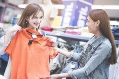 Mulheres que procuram a roupa imagens de stock