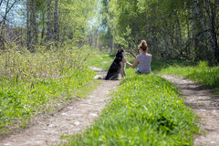 Mulheres que sentam-se com os cães na floresta Fotos de Stock Royalty Free