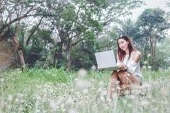 Mulheres que sentam-se na caixa de madeira e que trabalham com caderno Ela que trabalha no parque foto de stock royalty free