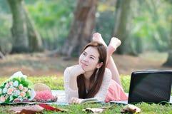 Mulheres que sentam-se na esteira de madeira e que pensam a alguém Foto de Stock