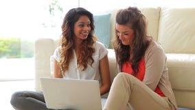 Mulheres que sentam-se na frente do sofá com portátil video estoque