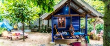 Mulheres que sentam-se no patamar da casa de campo pequena imagem de stock