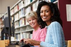Mulheres que trabalham em computadores na biblioteca Fotografia de Stock Royalty Free
