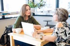 Mulheres que usam o portátil em uma cafetaria fotos de stock