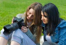 Mulheres que verific o viewfinder da câmera foto de stock