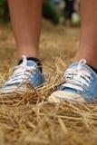 Mulheres que vestem as sapatas azuis que estão na palha do arroz Imagens de Stock Royalty Free