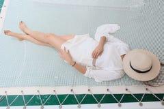 Mulheres que vestem um vestido branco que relaxa Fotografia de Stock