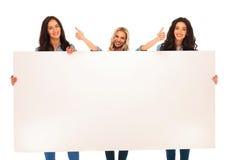3 mulheres recomendam o que lhe mostram na placa grande Imagens de Stock Royalty Free