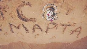 Mulheres ` s dia o 8 de março internacional número 8 feito do coco, das pedras e das flores Texto escrito na areia em tropical Imagens de Stock Royalty Free