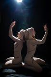 2 mulheres sedutores consideravelmente novas atrativas no corpo apertado coloriram o terno que olha acima as mãos na oração no pr Imagens de Stock Royalty Free