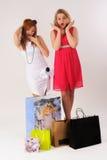 Mulheres surpreendidas com sacos de compras Imagens de Stock Royalty Free