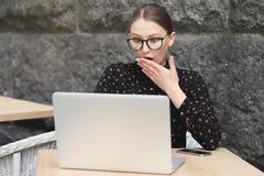 Mulheres surpreendidas que vestem os vidros, camisa preta no café que olha no portátil Foto de Stock