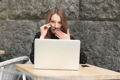 Mulheres surpreendidas que vestem os vidros, camisa preta no café que olha no portátil Fotografia de Stock Royalty Free