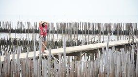 Mulheres tailandesas que andam apenas na ponte da passagem na floresta dos manguezais filme