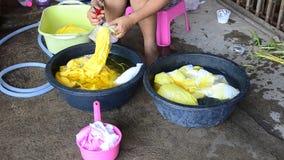 Mulheres tailandesas que lavam e roupa limpa após a tingidura do batik do laço vídeos de arquivo