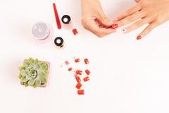 Mulheres tratamento de mãos e diplomatas que um prego dá forma durante o procedimento de extensões do prego com gel em casa Conce Foto de Stock